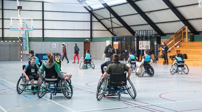 Adolescents en fauteuils roulants qui jouent au basketball