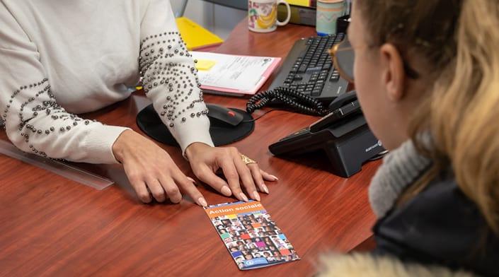 Une femme remet un livret d'information sur l'action sociale de la Ville