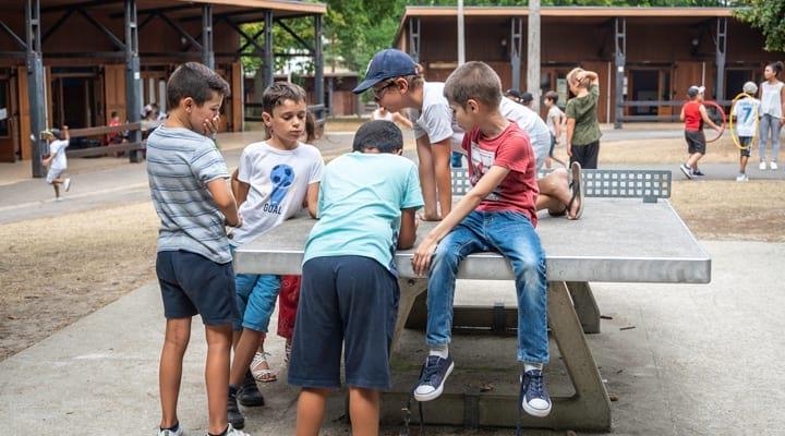Des enfants jouent sur une table de ping-pong