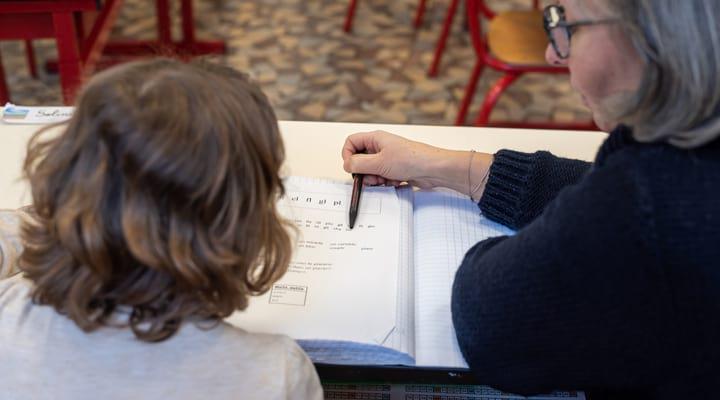 Une femme aide un enfant à faire ses devoirs