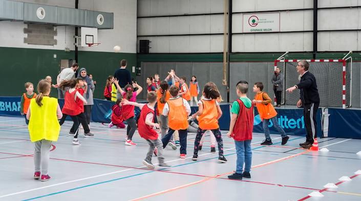 Des enfants font du sport dans un gymnase