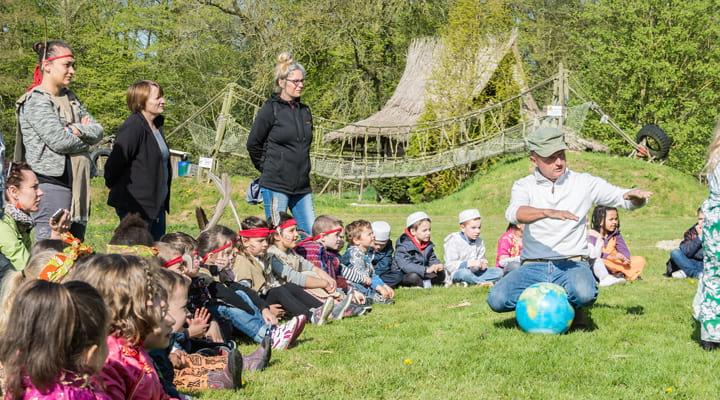 Des enfants déguisés à la ferme écoute un animateur