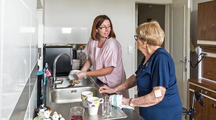 Une aide à domicile aide une senior chez elle
