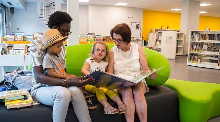 Une grand-mère lit un livre à sa petite fille et un autre enfant