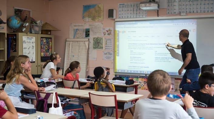 Un professeur montre un écran numérique aux élèves