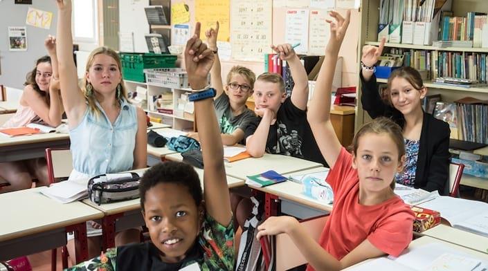 Des enfants lèvent le doigt