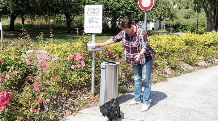 Une femme prends un sac à déjections canine