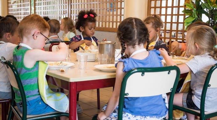 Des enfants mangent à la cantine