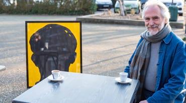 Philippe Ripoll avec une oeuvre de l'artothèque dans un café.