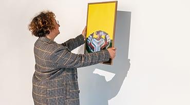 Une personne décroche une oeuvre d'un mur