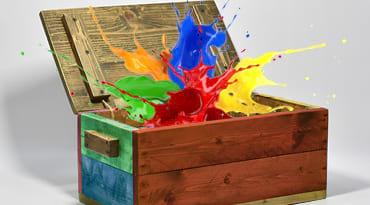 Une malle dont sort une explosion de peinture